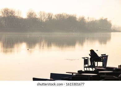 Silhouette of a person sitting alone on the river bank and smoking while looking at the other shore