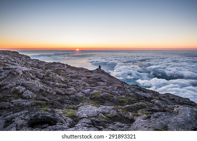 A silhouette of a person sitting on the edge on the top of the mountain above the clouds in early morning during the sunrise. A conceptual scene. HDR landscape