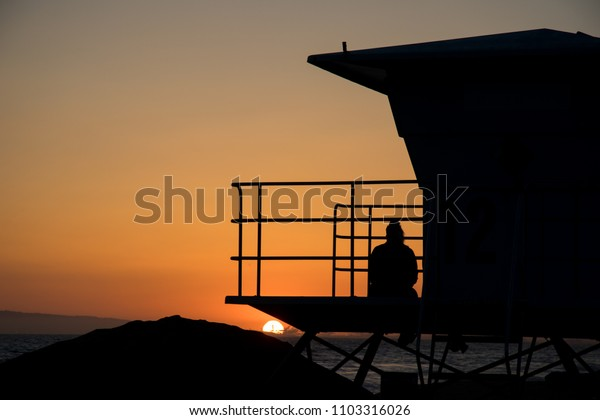 Silhouette of a person sitting on a lifeguard tower watching a bright orange sunset over the Pacific Ocean