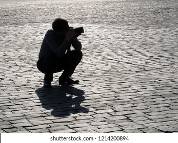 Silhouette of person with a SLR camera on the street. Man photographing in sunny day outdoor in the city, concept for paparazzi, photo reporter