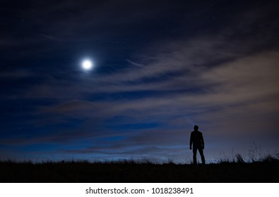 Silhouette of person standing atop a grassy hill with a light beam looking up at the milky way, moon, and clouds after sunset.