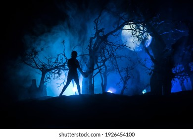 Silhouette of person standing in the dark forest. Horror halloween concept. strange silhouette in a dark spooky forest at night