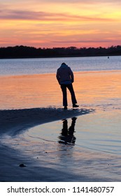 Silhouette of a person standing at the water's edge of a beach at sunset lifting one foot with a wet shoe out of the water