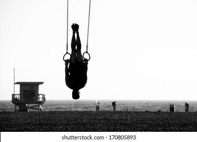 Silhouette of a person swinging on rings on the beach, Santa Monica Beach, Santa Monica, Los Angeles County, California, USA