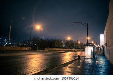 Silhouette of a person waiting in a city bus stop at night