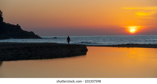 Silhouette of a person walking on jetty at sunset, Sayulita, Nayarit, Mexico