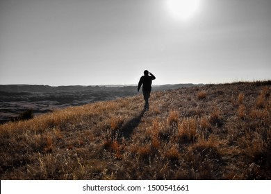 A silhouette of a person walking through rolling hills covered in green and yellow golden grass. The sun in a grey gloomy sky above beams down on hiker casting a shadow on the ground behind him