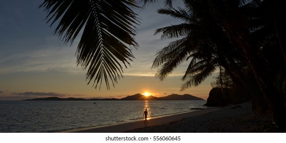 Silhouette of a person walks on the beach during tropical sunset over the Yasawa Islands, Fiji. Real people copy space