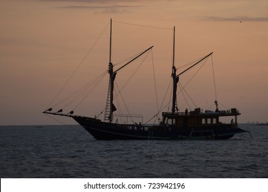silhouette phinisi wooden ship at sunset, a traditional wooden boat from Sulawesi Indonesia