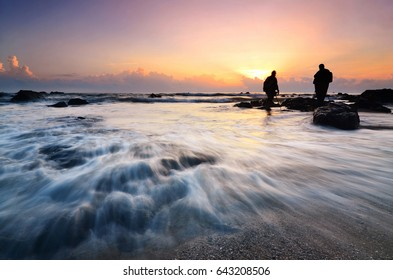 Silhouette of photgraphers shooting the sunrise at a beach in Te