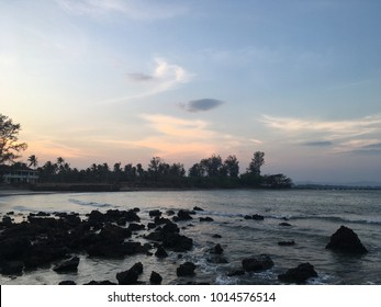 Silhouette photo of beautiful sunset seascape during twilight time with many rocks.Beach sunset concept.