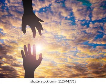 The Silhouette photo of hand to hand. One hand helps another. This photo communicate about hope and supporting and also helping. International day of peace.