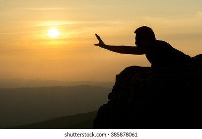 A silhouette photo of a man laying down by the edge of the cliff reaching out his arm trying to  grab the sun