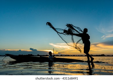 silhouette photo. The old fisherman casting the net for fish to cook for a little grandson in the sunset.