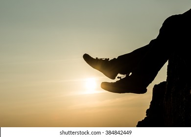 A silhouette photo of a pair of feet playing with the sun like playing football (soccer)