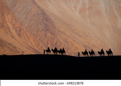 The silhouette photo of people riding a camel in the desert. With magnificent mountain views in Ladakh, Leh, India