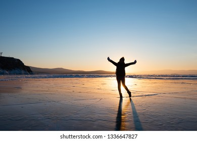 Silhouette photo of woman is walking and raise her hand on frozen lake at Baikal