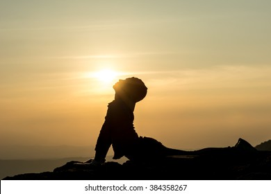 A silhouette photo of a woman who is doing Bhujangasana aka. cobra posture (yoga pose) and trying to kiss the sun