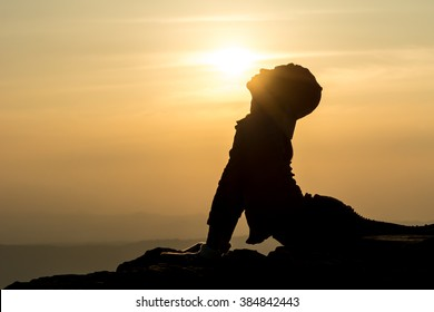 A silhouette photo of a woman who is doing Bhujangasana aka. cobra posture (yoga pose) and trying to kiss the sun (closer version)