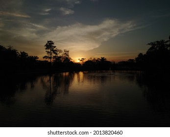 A silhouette photograph of a sunset at a lake with trees around the lakeside.