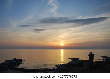 Silhouette of a photographer capturing a beautiful sunset by seaside