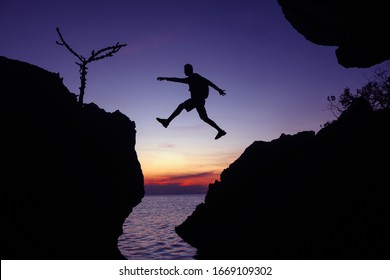 Silhouette of the photographer jumping over the stone at sunset ,Man Jumping between rocks on tropical Sea at twilight sky.