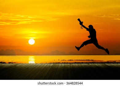Silhouette of photographer jumping with sunset, seascape.
