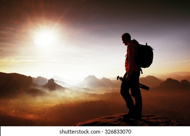 Silhouette of photographer overlooking a blanket of fog over valley to sun
