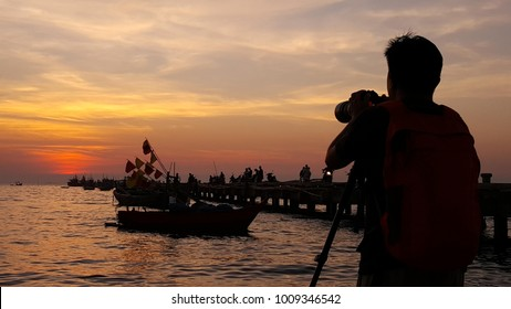 A silhouette of a photographer shooting a fishing boat at sunset on the beach.