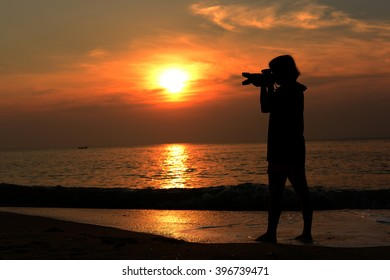 Silhouette photographer sitting on the beach with sun