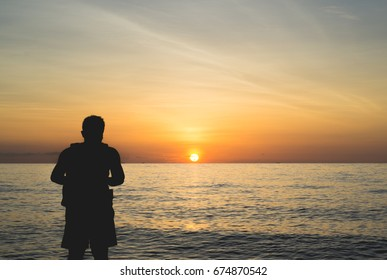 Silhouette of the photographer standing among the sunlight at the sea in the morning.