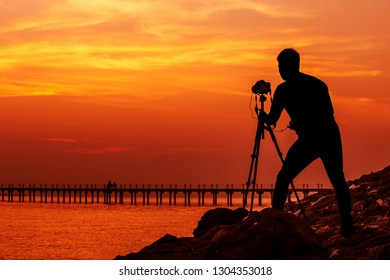 Silhouette of photographer standing with camera on tripod over sunset time ,with filtered warm tone ,image for happy time concept.