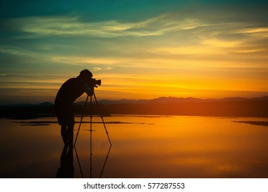 Silhouette Photographer take photo beautiful seascape at sunset in Thailand. Vintage tone