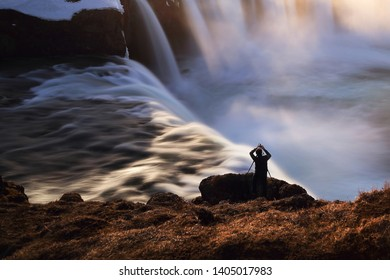 Silhouette photographer taking a photo beautiful scenery of Godafoss in Iceland.Godafoss waterfall is very popular for photographers and tourists. Activity and travel concept.