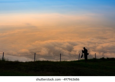 Silhouette of photographer taking photo on Cloud bright orange sunrise, phu tubberk Thailand
