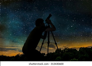 Silhouette of photographer is taking photos of stars and night sky with camera on tripod.