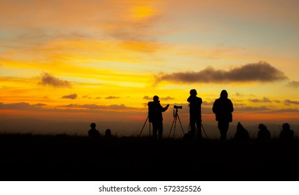 silhouette of photographer taking picture of landscape during sunset.