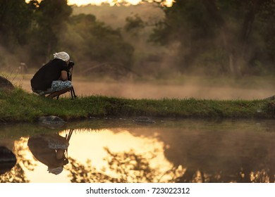 silhouette of photographer taking picture of landscape during sunset. Lifestyle Concept