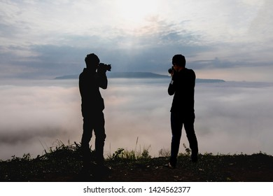 Silhouette of photographer or Traveller using a professional DSLR camera take photo beautiful landscape at the clouds from high up in the hills at Khao Takhian Ngo view point at Khao Kho;Phetchabun