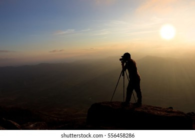 silhouette of a photographer who shoots landscape in twilight