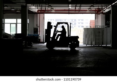 Silhouette photos: the driver of a factory building is carrying a forklift truck.