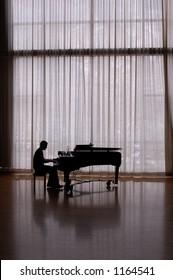 silhouette pianist in sunlit studio