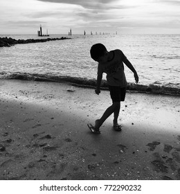 Silhouette picture of boy walking by the beach