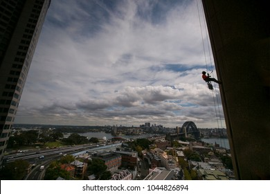 Silhouette picture of construction rope access worker wearing a hard hat, full body safety harness working at height, abseiling off from the high rise building near circular quay, Sydney, Australia