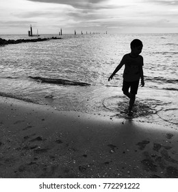 Silhouette picture of kid playing water at the beach