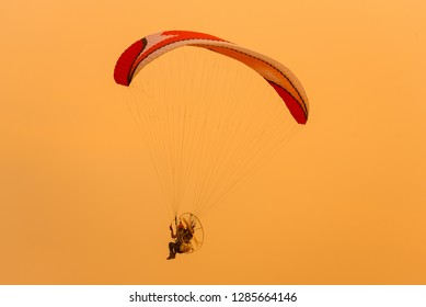 Silhouette picture of the Paramotor is flying through soft sunlight sunset sky