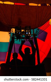 Silhouette of pilot in hot air balloon basket using burner with beautiful colored envelope in the background, backlit by sunlight photography