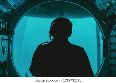 silhouette of a pilot in submarine cockpit under water