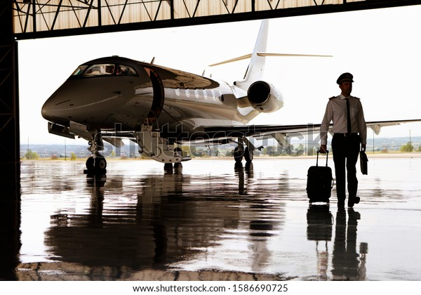 Silhouette of pilot walking away from private jet in hangar