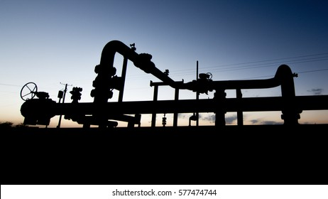 Silhouette of a pipeline manifold jump over in the oilfield at sunset blue hour